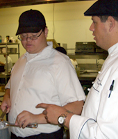 Dan Escobar '04, program development manager for Kitchens With Mission, works with a student.