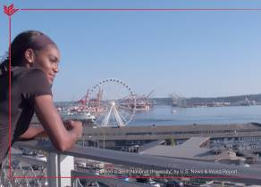 A student looking out on Elliot Bay with the Seattle Great Wheel in the background