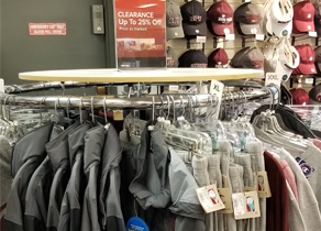 Rack of jackets and sweats with hats in the background in the SPU bookstore.