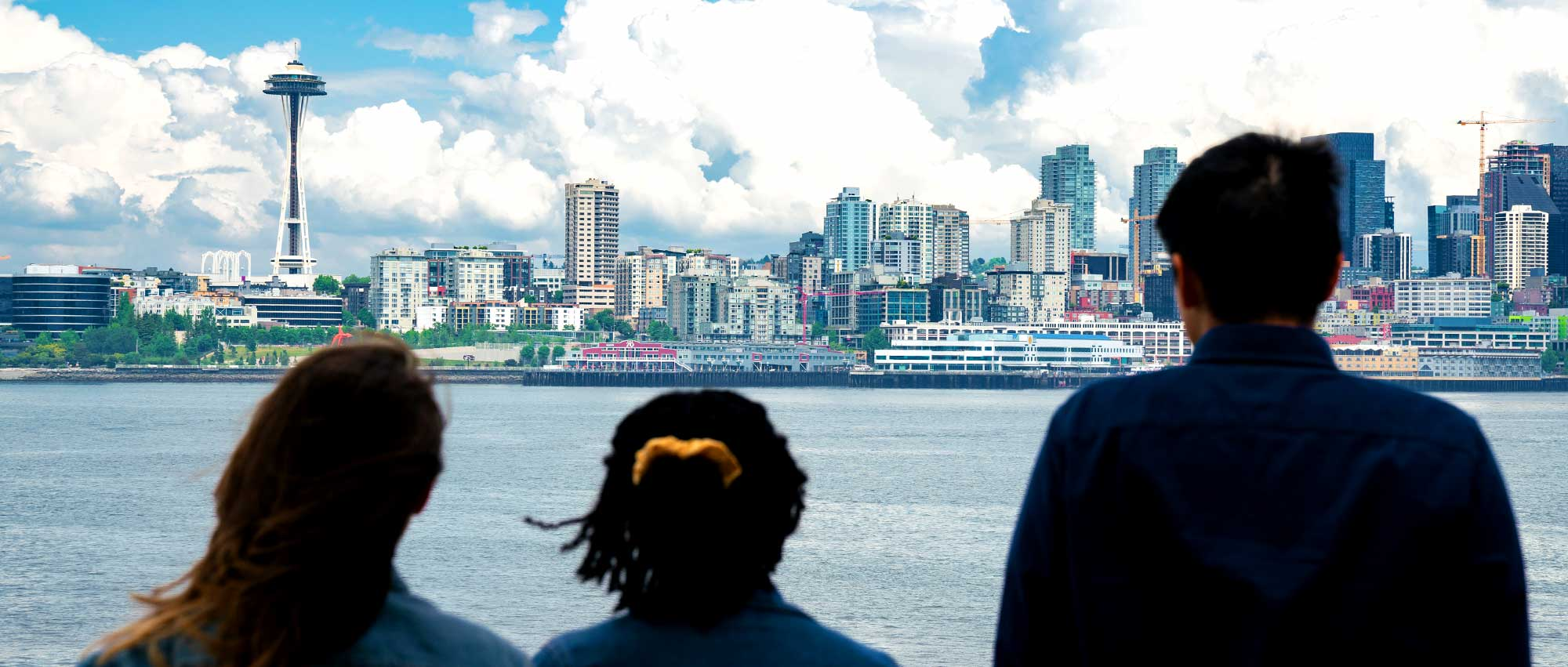 Three students looking at the Seattle skyline