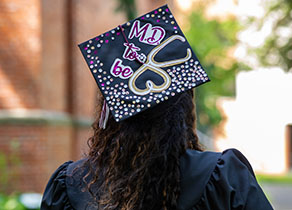 "An SPU graduate with a decorated mortarboard reading ""M.D. to be"""