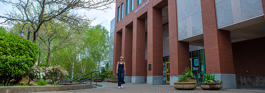 student walking in front of Ames Library