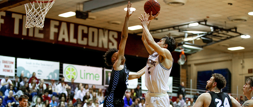 An SPU men's basketball player shoots into the hoop while an opposing player goes up for a block.