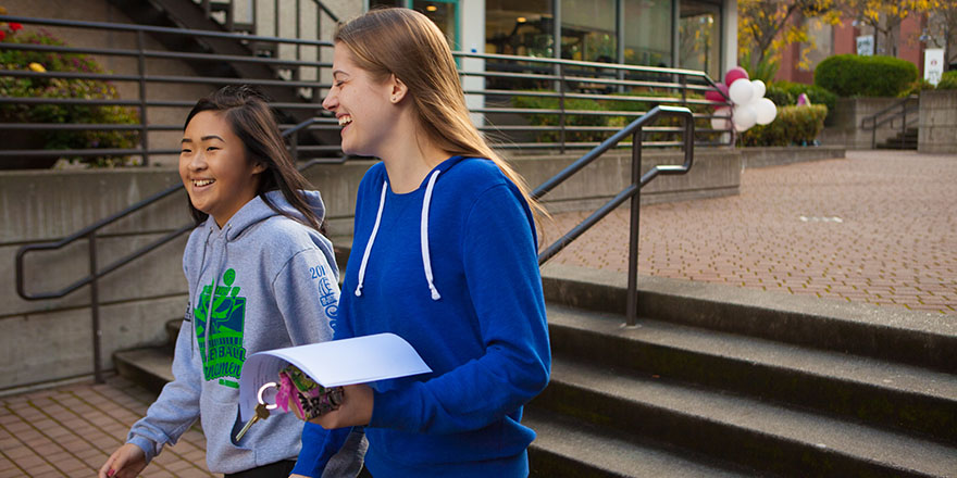 SPU students laugh while walking near Gwinn Commons