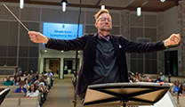 Christopher Hanson conducting with arms outstretched, holding a baton, with his eyes closed