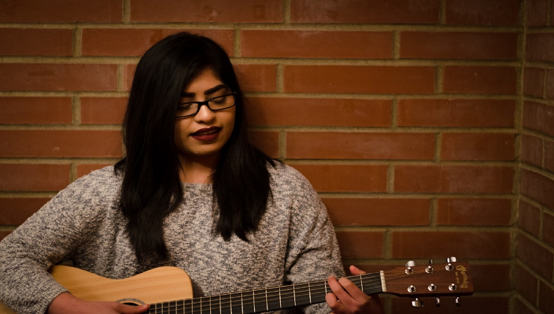 Student Ruth Rodriguez Playing the Guitar