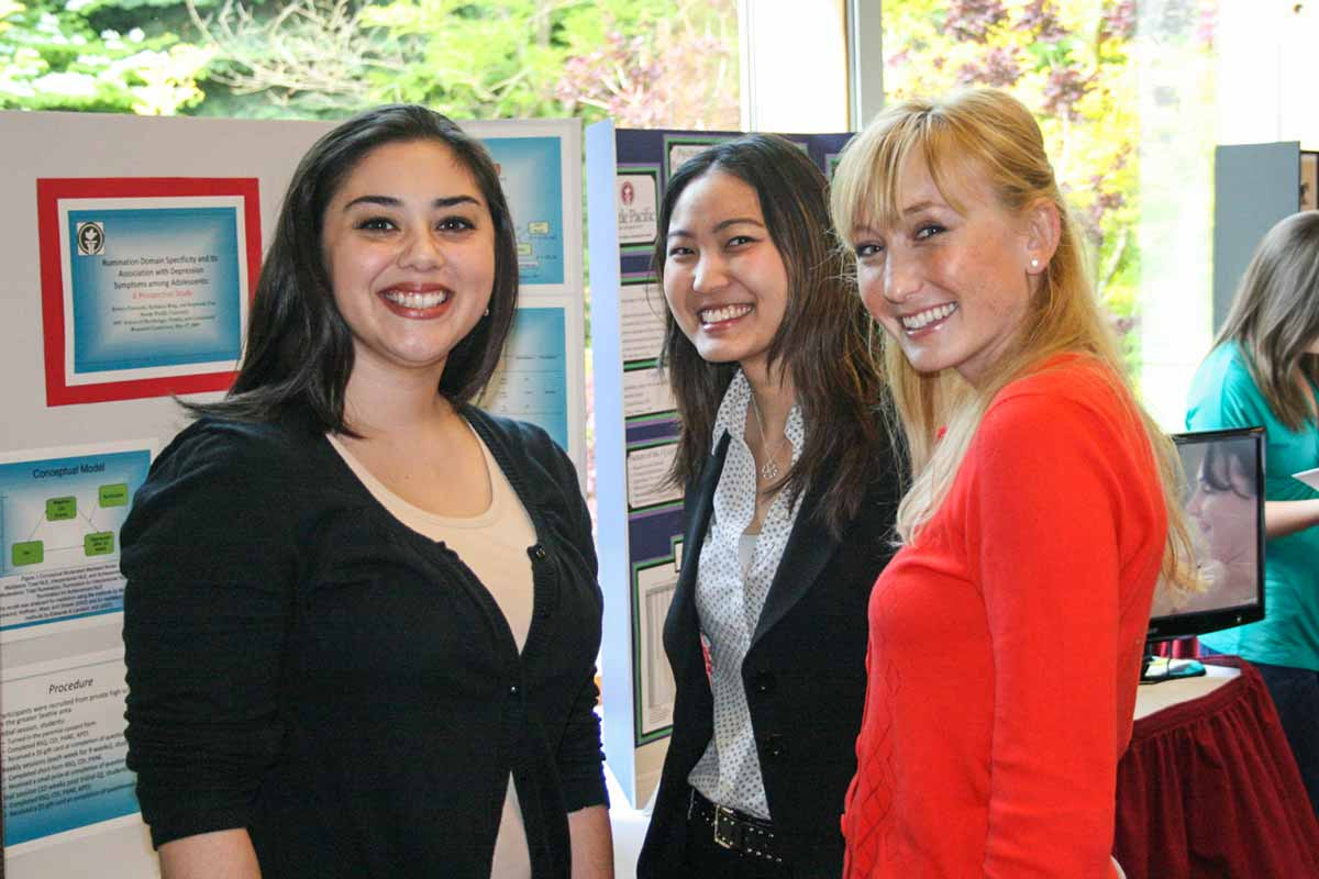 Three students at a research presentation