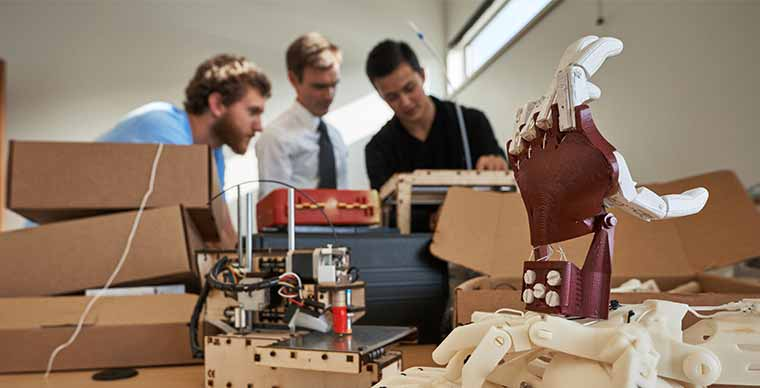Mechanical Engineering students working on a 3-D printed prosthetic hand
