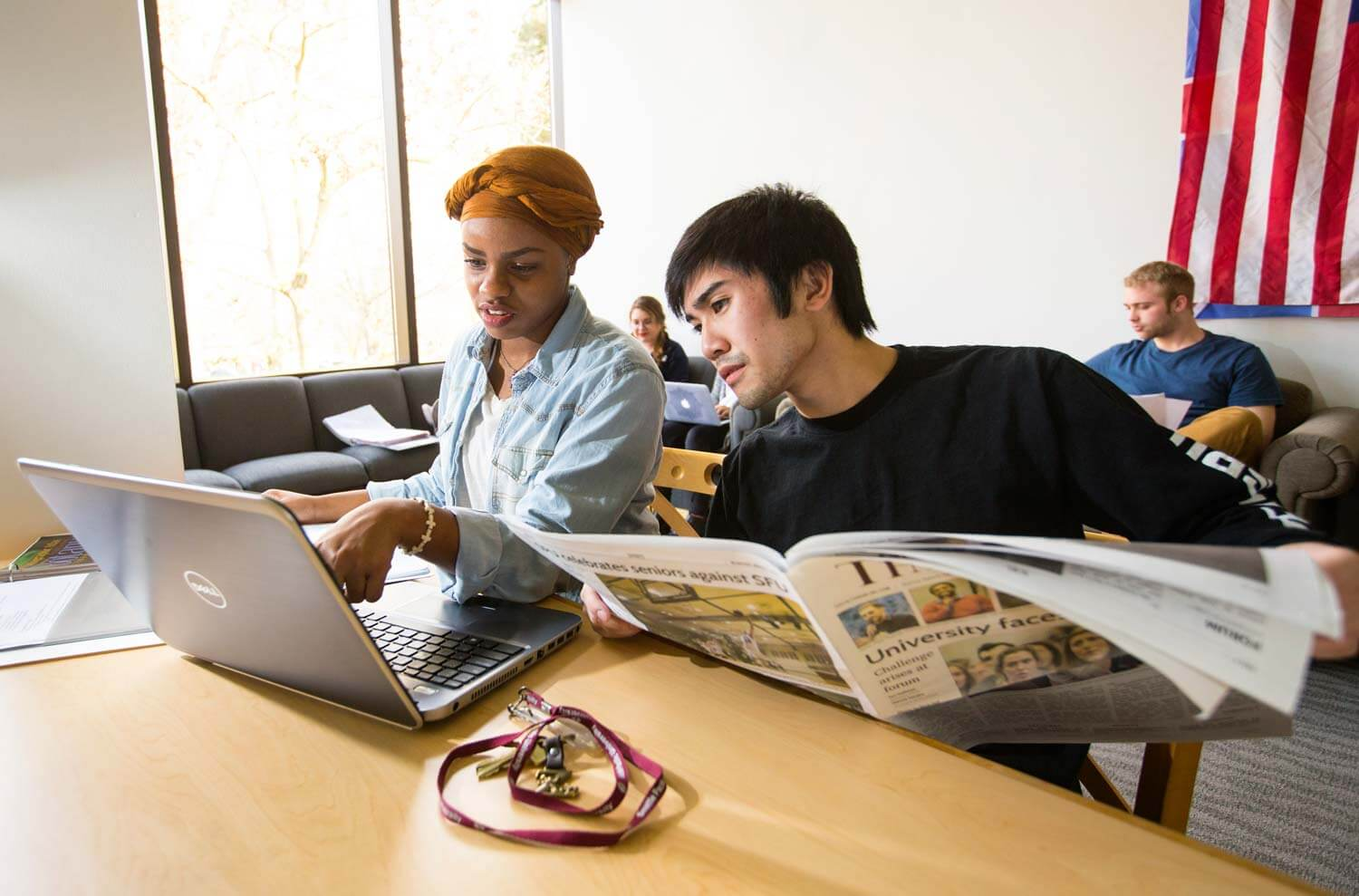 Students looking at laptop and newspaper