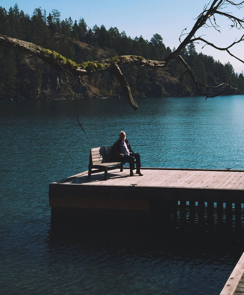 Eugene Peterson sits on a dock by a still lake