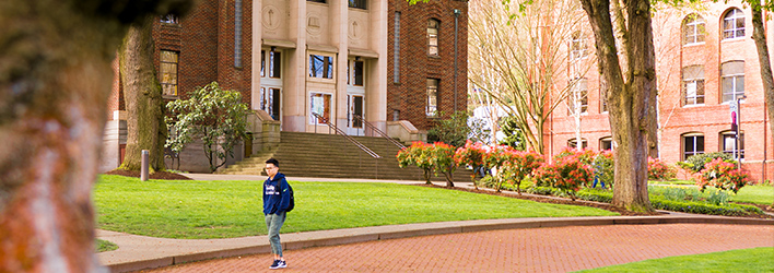 Banner image for degree programs, student walking on campus