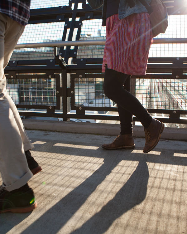 people walking over a pedestrian bridge