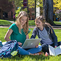 Two SPU students do homework in Tiffany Loop on a sunny day