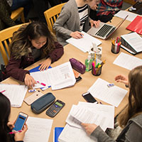 SPU students gather around a desk, studying hard for finals