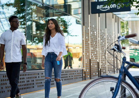 two people walk past Amazon Go