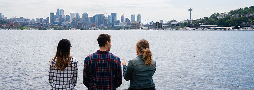 Three SPU students look out across Lake Union towards the Seattle skyline