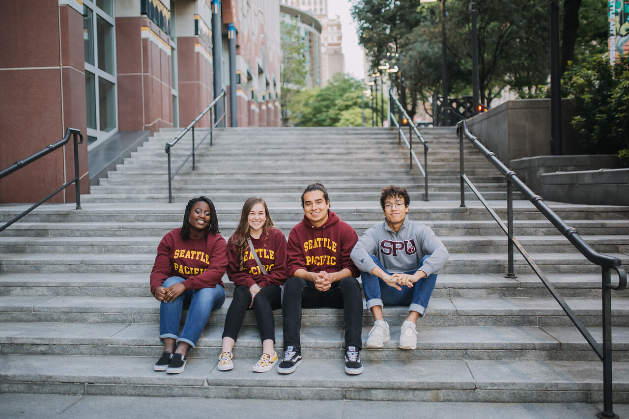 Students sitting on stairs, wearing SPU sweatshirts