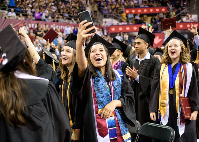 student takes a selfie at graduation