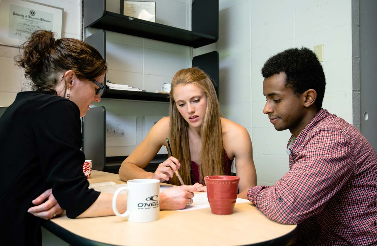 Associate Professor of Philosophy Rebekah Rice meets with philosophy majors Kelsey Tuohy and Qadar Omar.