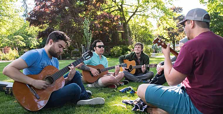 5 Students sitting on the grass at campus playing guitar