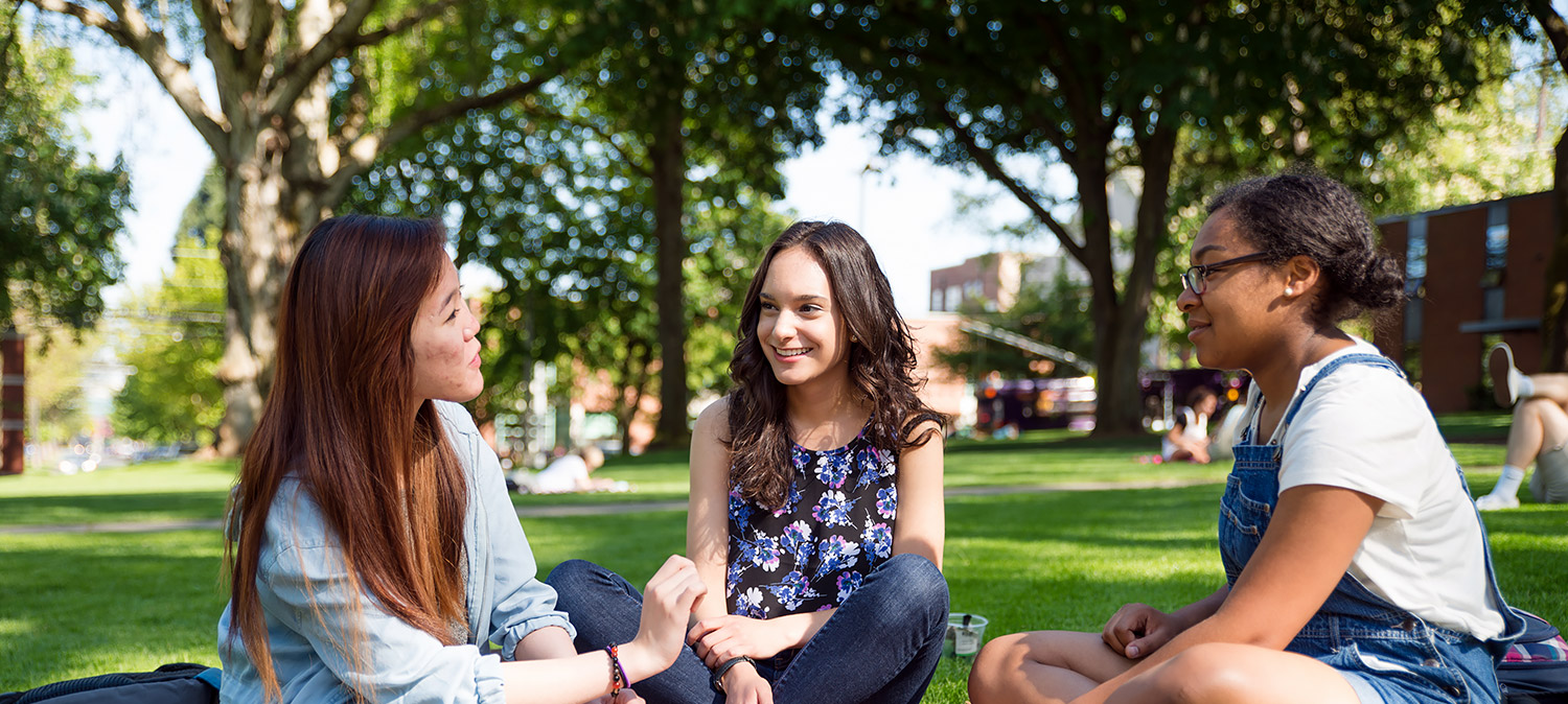 Three students talking while sitting on the grass in Tiffany Loop/